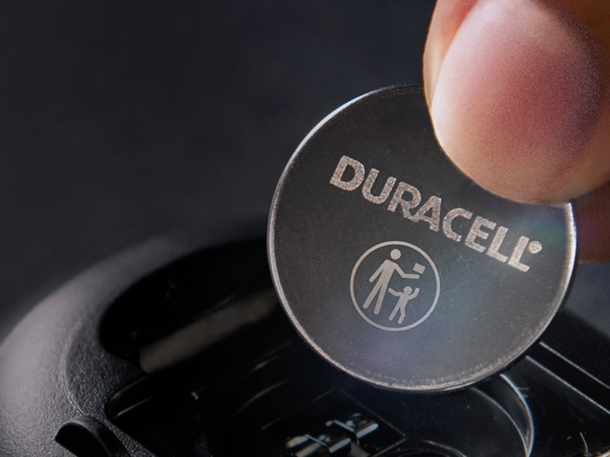 Coin battery held by fingers